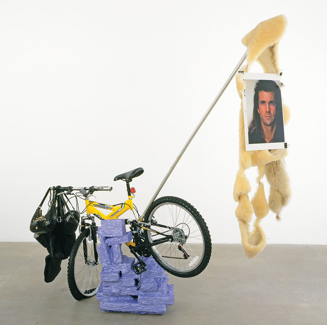"Rachel Harrison, Huffy Howler, 2004, wood, polystyrene, cement, acrylic, Huffy Howler bicycle, handbags, rocks, stones, gravel, brick, one sheepskin, two foxtails, metal pole, wire, ink-jet print, binder clips, 84 × 84 × 30""."
