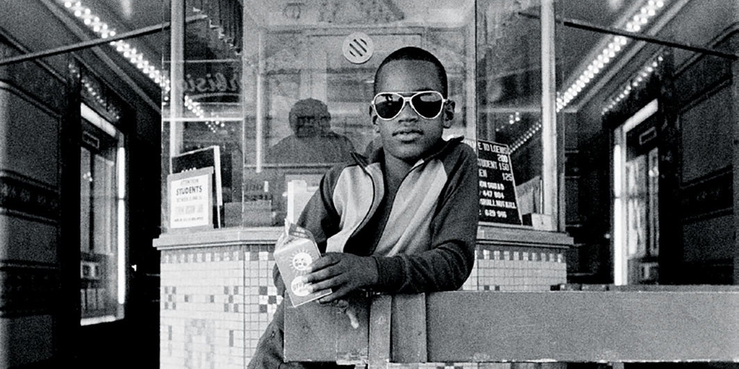 "Dawoud Bey, A Boy in Front of the Loews 125th Street Movie Theater, Harlem, NY, 1976, gelatin silver print, 14 × 11""."