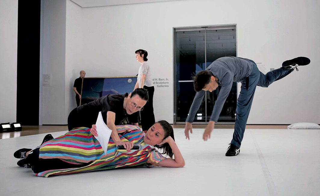 Yvonne Rainer, The Concept of Dust, or How do you look when there's nothing left to move?, 2015. Performance view, Werner and Elaine Dannheisser Lobby Gallery, Museum of Modern Art, New York, June 2015. Foreground, from left: Yvonne Rainer, Patricia Hoffbauer, Keith Sabado. Background: Pat Catterson. Photo: Julieta Cervantes.