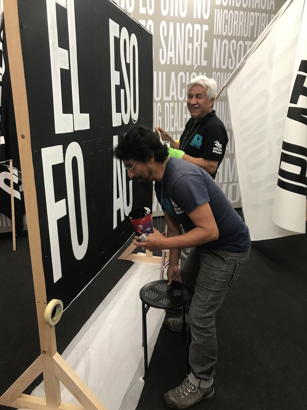 Sign painters for Erick Beltrán's Nothing But the Truth project at LABOR's Material booth.
