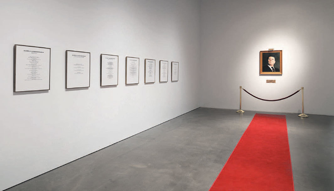 "View of ""Hans Haacke: All Connected,"" 2019–20. From left: Solomon R. Guggenheim Museum Board of Trustees, 1974; Öelgemälde, Hommage à Marcel Broodthaers (Oil Painting: Homage to Marcel Broodthaers), 1982. Photo: Dario Lasagni. © Hans Haacke/Artists Rights Society (ARS), New York/VG Bild-Kunst, Bonn."