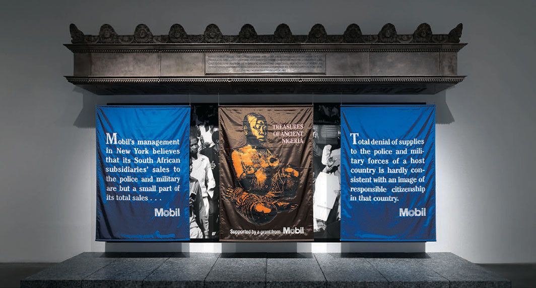 "Hans Haacke, MetroMobiltan, 1985, fiberglass, three banners, photomural, 11'8"" × 20' × 5'9"". Installation view, 2019. Photo: Dario Lasagni. © Hans Haacke/Artists Rights Society (ARS), New York/VG Bild-Kunst, Bonn."
