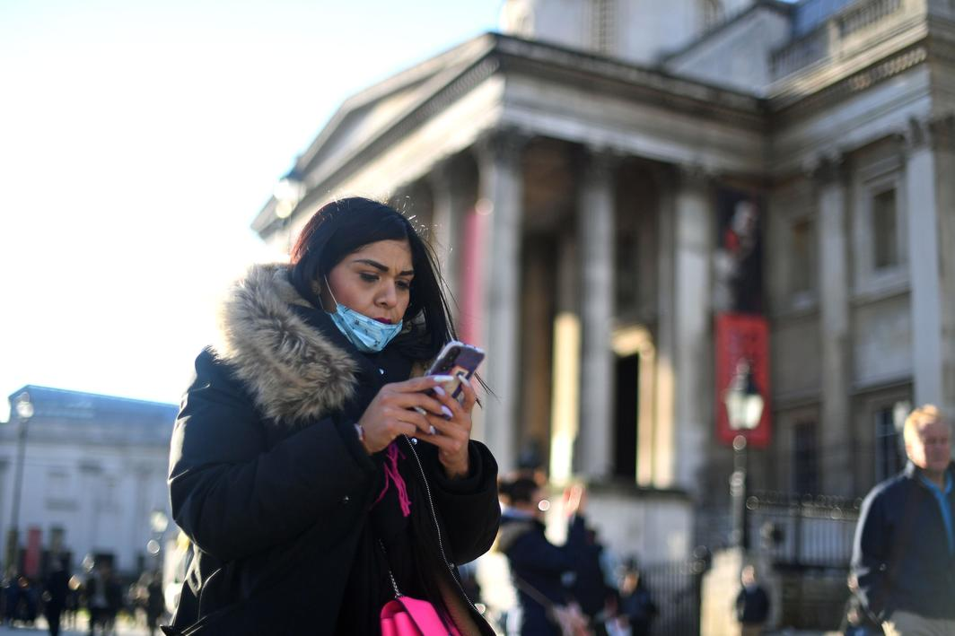A woman wearing a face mask on her phone outside the National Gallery in Trafalgar Square, London. Photo: PA Images/Alamy.