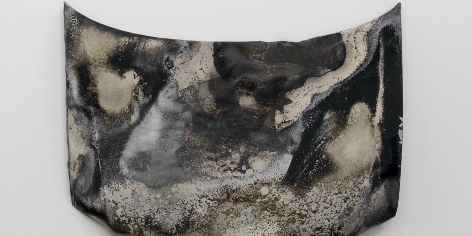 "Rubén Ortiz Torres, Burnt, 2020, urethane and crystals on car hood, 48 x 62 x 7""."