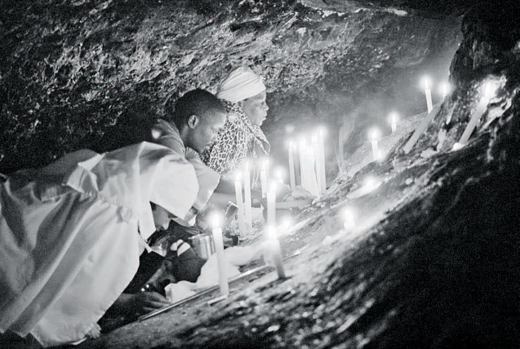 "Santu Mofokeng, Mthunzi and Miesie Making Supplications to the Ancestors Inside the Motouleng Sanctum - Free State, 2008, gelatin silver print. From the series ""Chasing Shadows,"" 1996–2006. © Santu Mofokeng Foundation/Lunetta Bartz, MAKER, Johannesburg."