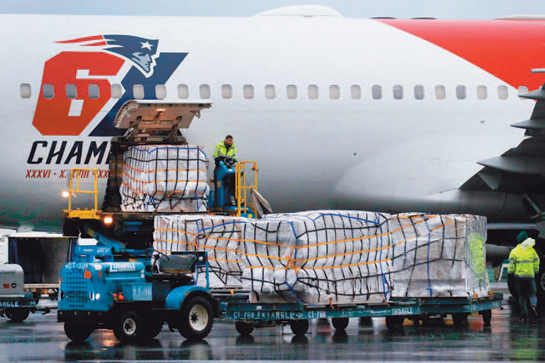 Pallets of N95 respirator masks from China are unloaded from the New England Patriots' airplane, Logan Airport, Boston, April 2, 2020. Photo: Elise Amendola/AP/Shutterstock.