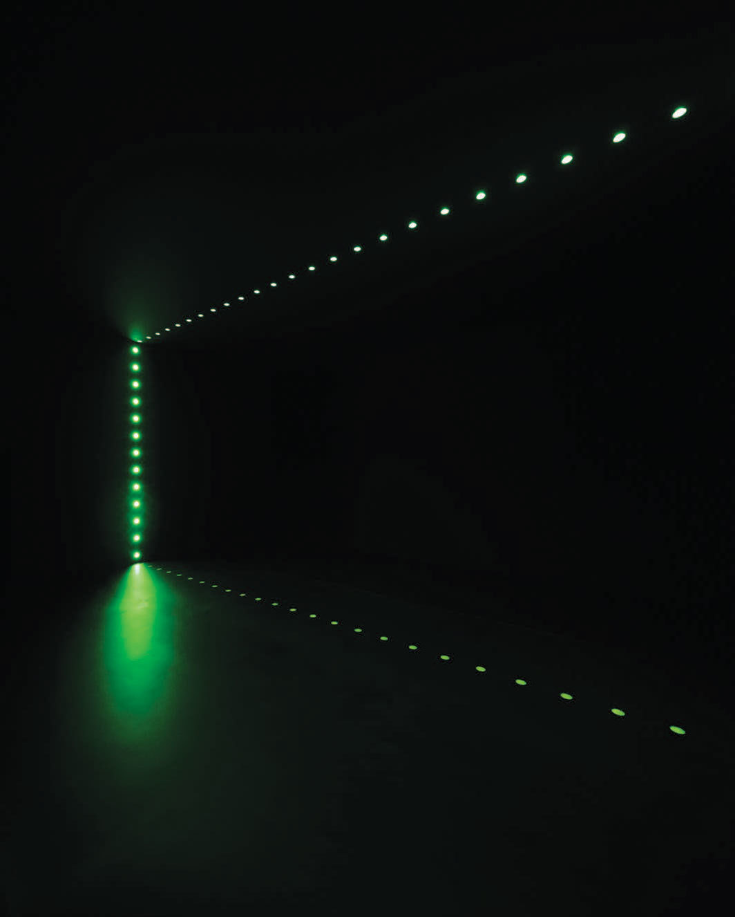Lucio Fontana, Ambiente spaziale (Spatial Environment), 1966/2020, rectangular room, two corridors to enter and exit, walls and ceiling lined with black fabric, flooring in polyurethane foam covered in rubber, backlit holes with green neon crystal tubes. Installation view.