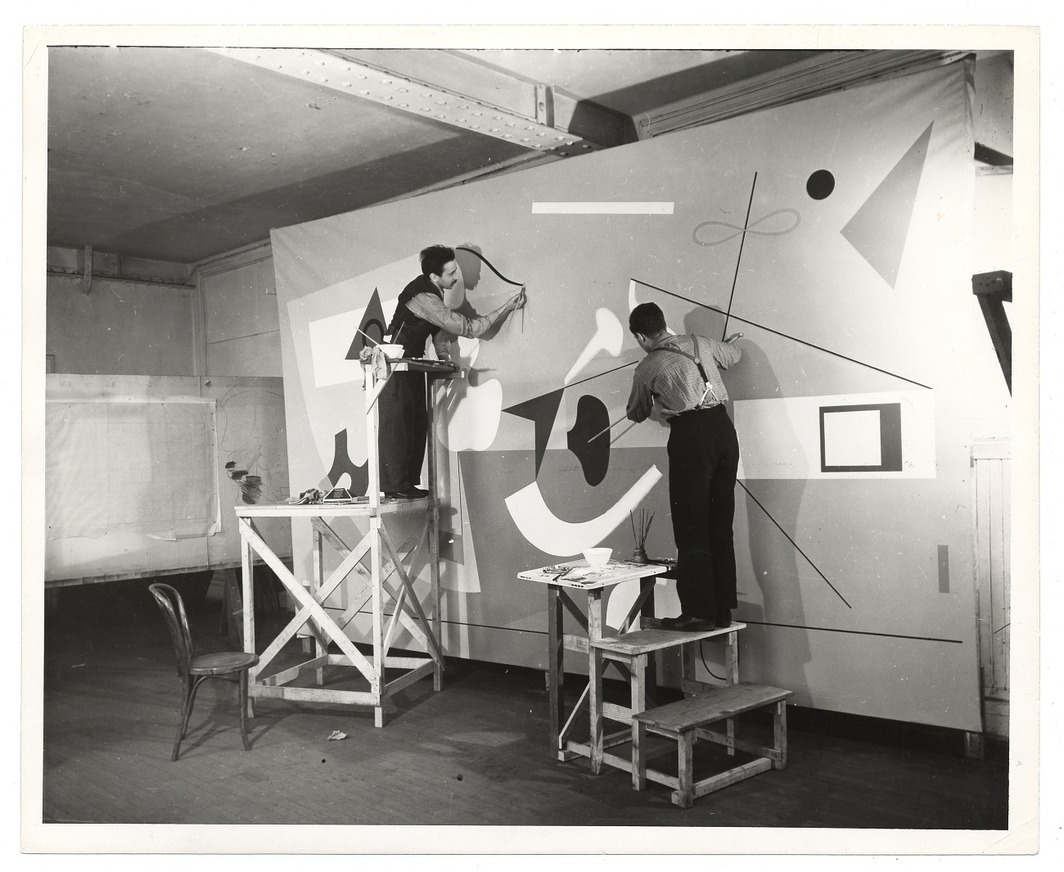 Ilya Bolotowsky working on Williamsburg Housing Project mural with assistant John Joslyn, 1938, photograph, 9 3/4 x 8 1/4''. Photo: Archives of American Art, Smithsonian Institution.