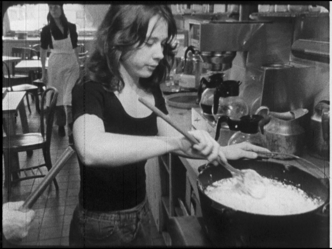 Still image of Tina Girouard from Food by Gordon Matta-Clark, 1972, 16 mm film transferred to HD video, black and white, sound, 43 minutes.