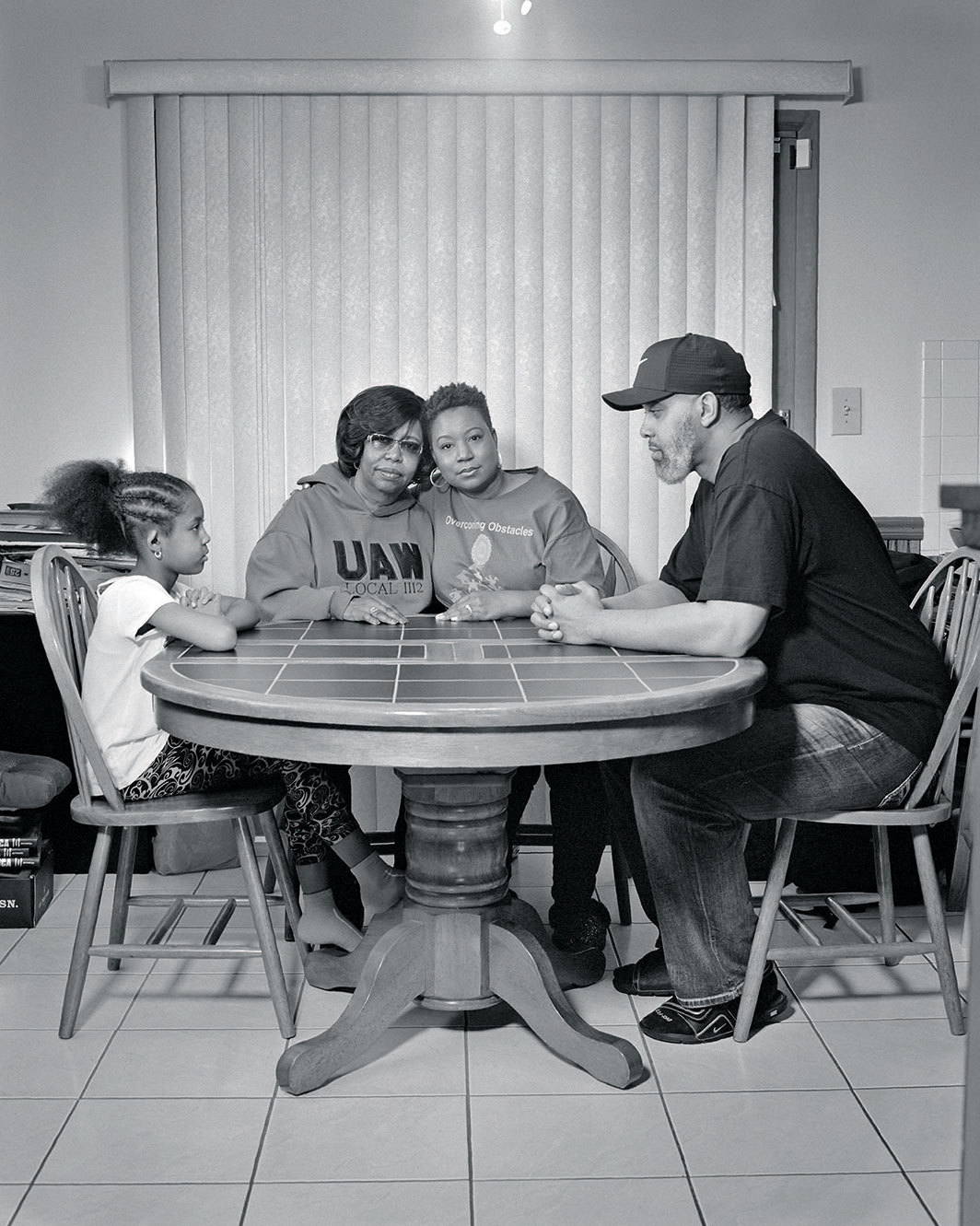 "LaToya Ruby Frazier, Sherria Duncan, UAW Local 1112, at her kitchen table with her mother Waldine Arrington, her daughter Olivia, and her husband Jason, (23 years in at GM Lordstown Complex, trim and paint shop), Austintown, OH, 2019, gelatin silver print, 20 × 16"". From the series ""The Last Cruze,"" 2019."