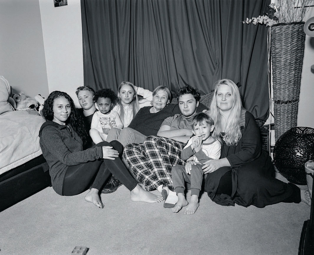 "LaToya Ruby Frazier, Angela Ralston, UAW Local 1714, at home with her mother Nancy Simmons; her children Aneesa, Seth, and Colin Ralston, Marena Wolford, and Greyson Simmons; and her granddaughter Eliana Hall (Transition Center Customer Service Representative, 9.9 years in at GM Lordstown Complex, West Plant fabrication body shop), Girard, OH, 2019, gelatin silver print, 16 × 20"". From the series ""The Last Cruze,"" 2019."