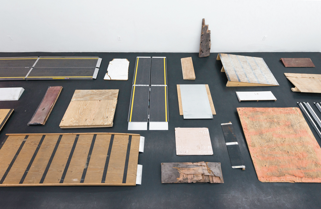 "View of ""Park McArthur: Ramps,"" 2014, Essex Street, New York. [A view from above of temporary ramps of different sizes and materials in a loose grid on a black concrete floor. One small weather-worn wooden ramp leans against the room's white wall.]"