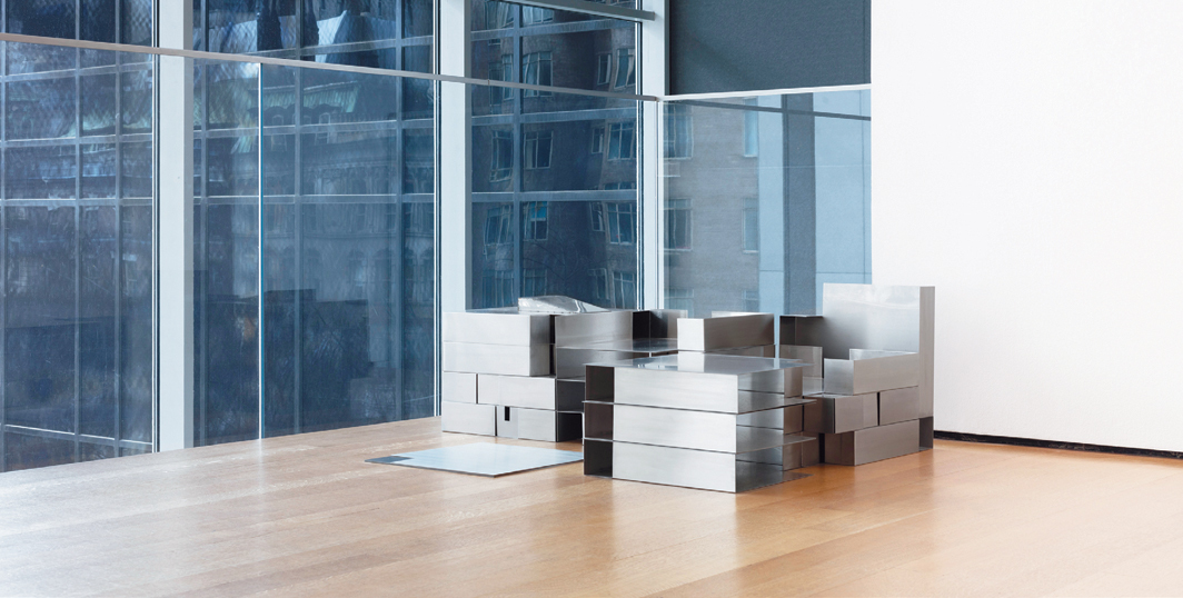 Park McArthur, STUDIO/HOME, 2018, stainless steel. Installation view, Museum of Modern Art, New York. [A sculpture displayed on the floor in front of a corner formed by windows and a gallery wall. The sculpture is made of similarly-sized metal trays arranged to resemble a small-scale building complex.]