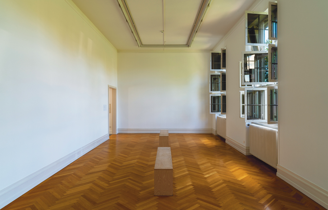 "View of ""Park McArthur: Kunsthalle_guests Gaeste.Netz.5456,"" 2020, Kunsthalle Bern, Switzerland. [A view of a windowed gallery with white walls, crown molding and wooden parquet flooring lit by daylight. Two unpainted wooden museum benches sit parallel to the open windows.]"