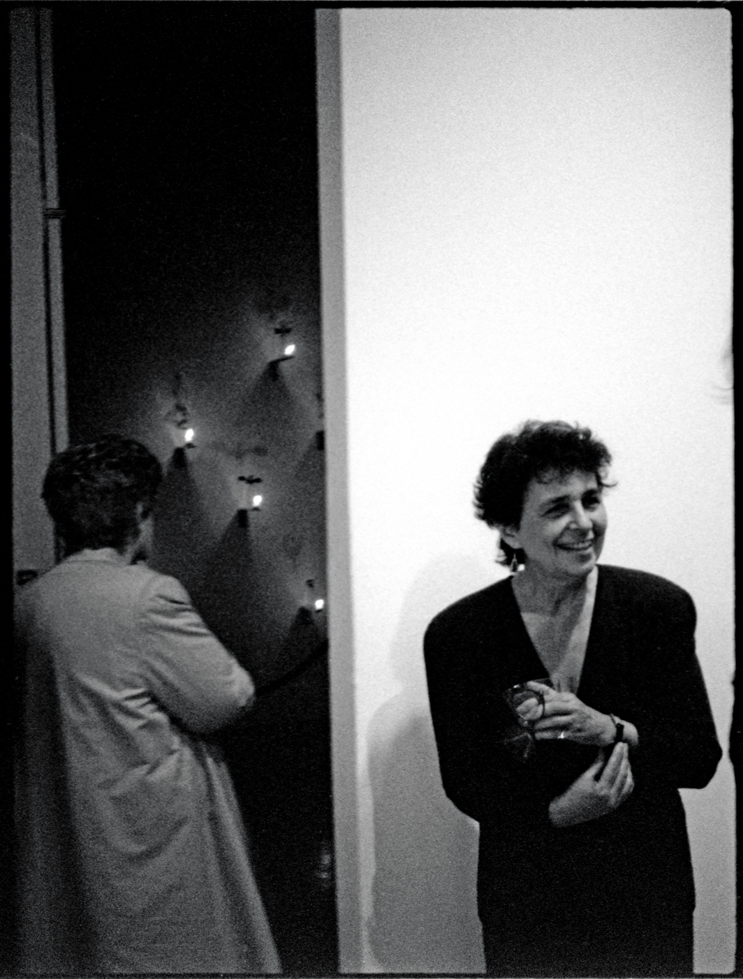 "Luciano Perna, Ileana Sonnabend looking at a Christian Boltanski installation and Marian Goodman, Marian Goodman Gallery, New York, 1987, ink-jet print, 22 × 17""."