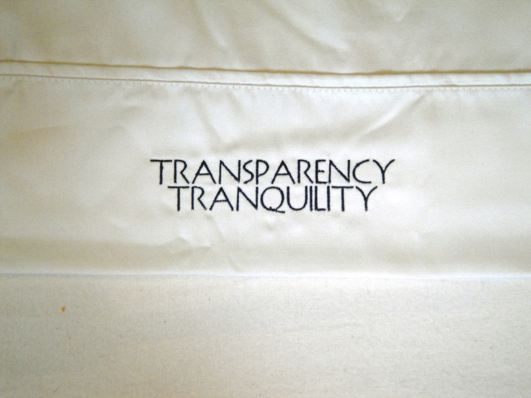 "A close-up of the hemmed trim on a white pillowcase has been embroidered in the center, in navy all caps. One line reads ""TRANSPARENCY,"" and the line underneath reads ""TRANQUILITY."""