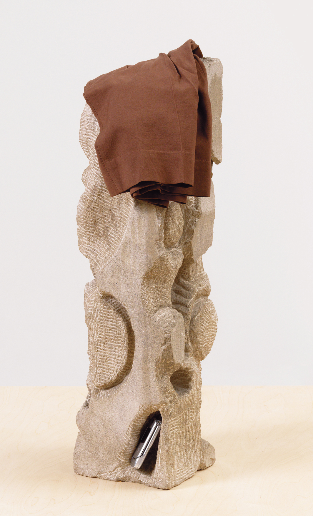 "Arnold J. Kemp, Nineteen Eighty-Four, 2020, limestone, tailored shorts made by the artist's grandfather (Arnold J. Kemp), flip phone from a performance featuring the artist's father (Howard J. Kemp), 31 × 8 1⁄4 × 8 1⁄4""."