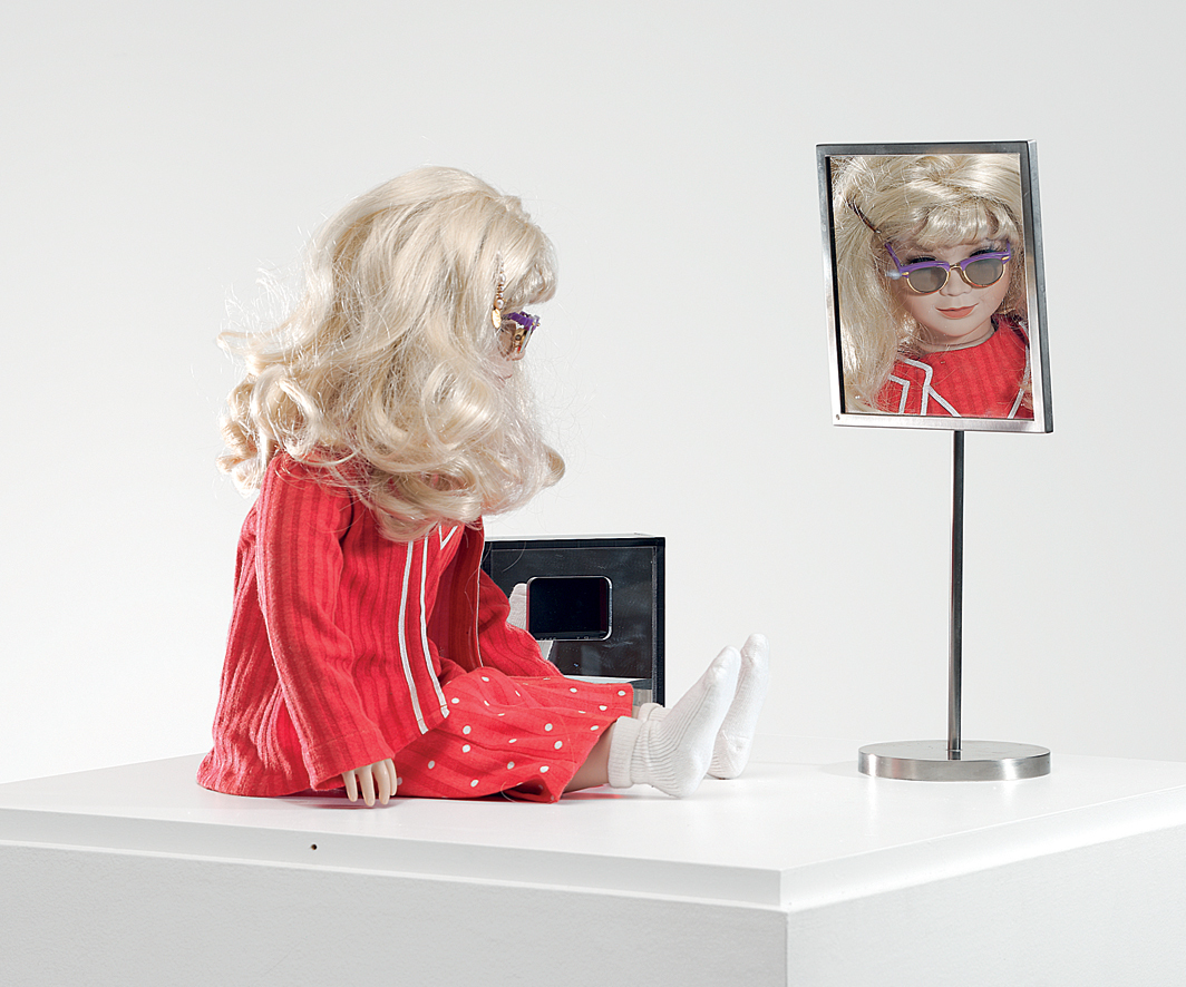 "Lynn Hershman Leeson, CyberRoberta, 1996, doll, clothing, glasses, webcams, surveillance camera, mirror, telerobotic hardware, programming, approx. 17 3/4 × 17 3/4 × 7 7/8""."