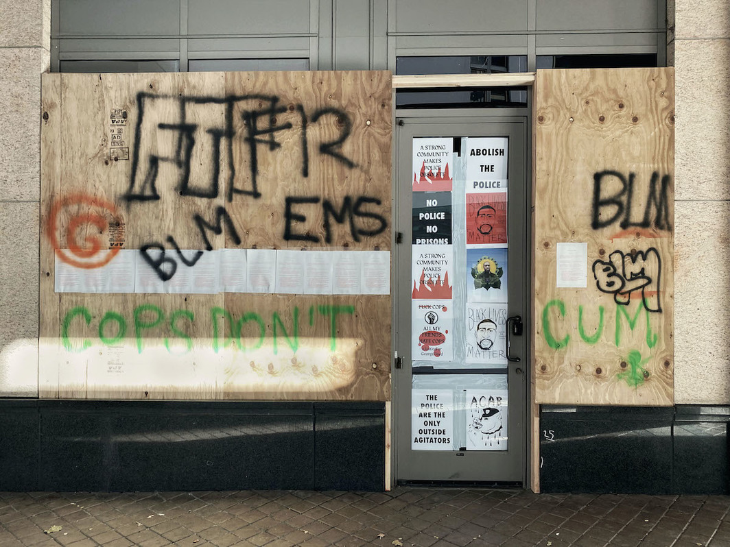 """Documentation of a Performing Pro Arts COMMONS action on the gallery's back entrance during the summer of 2020. Oakland city employees buffed the boards with white paint the following day to prepare for """"sanctioned images."""" Courtesy of Pro Arts Gallery and COMMONS."""