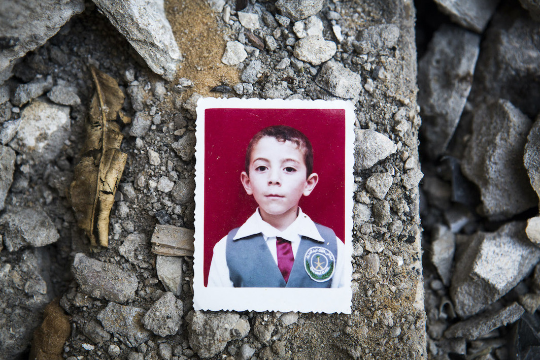 A photo of Abdallah Abdel Hadi Al Majdalawi, 13, placed on the ruins of his home in Jabaliya, Gaza Strip, March 19, 2015. Abdallah was killed alongside his brother Abdelrazek, 19, and his cousins Rawan, 9, and Mahmoud, 8, by an Israeli attack on August 3, 2014. Photo: Anne Paq.