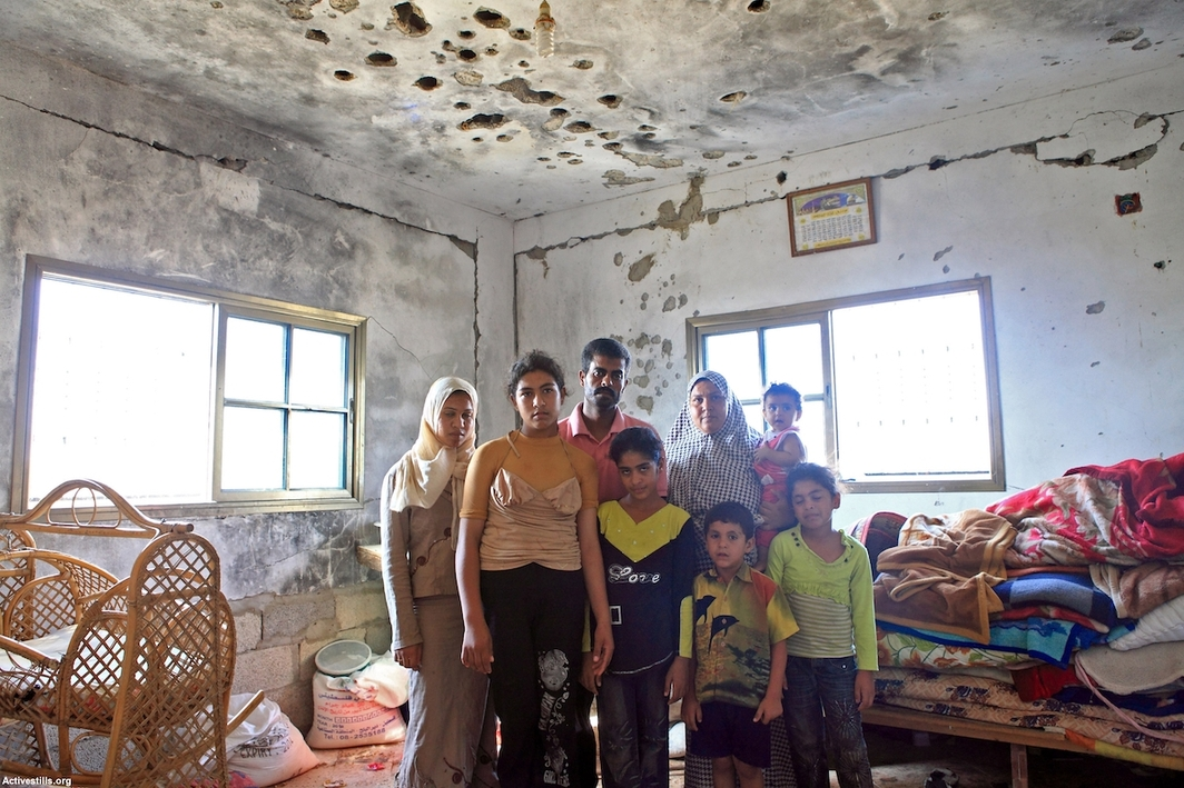 A Palestinian family standing inside their home, which was shelled during Operation Cast Lead in 2008/2009. The house became habitable once again only ten months after the operation. Beit Hanoun, Gaza Strip, August 2010. Photo: Anne Paq.
