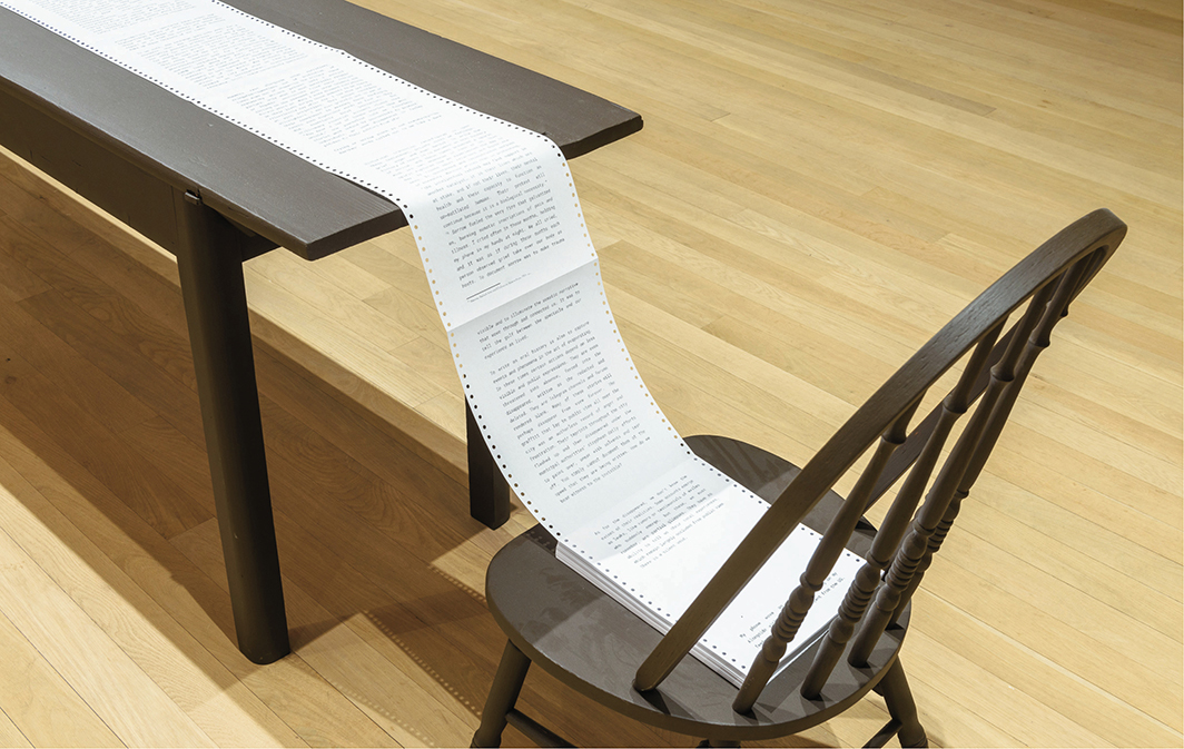 Tiffany Sia, The Bastard Scroll, 2021, ink on continuous-feed dot-matrix paper, wooden table, chair. Installation view, Artists Space, New York. Photo: Filip Wolak.