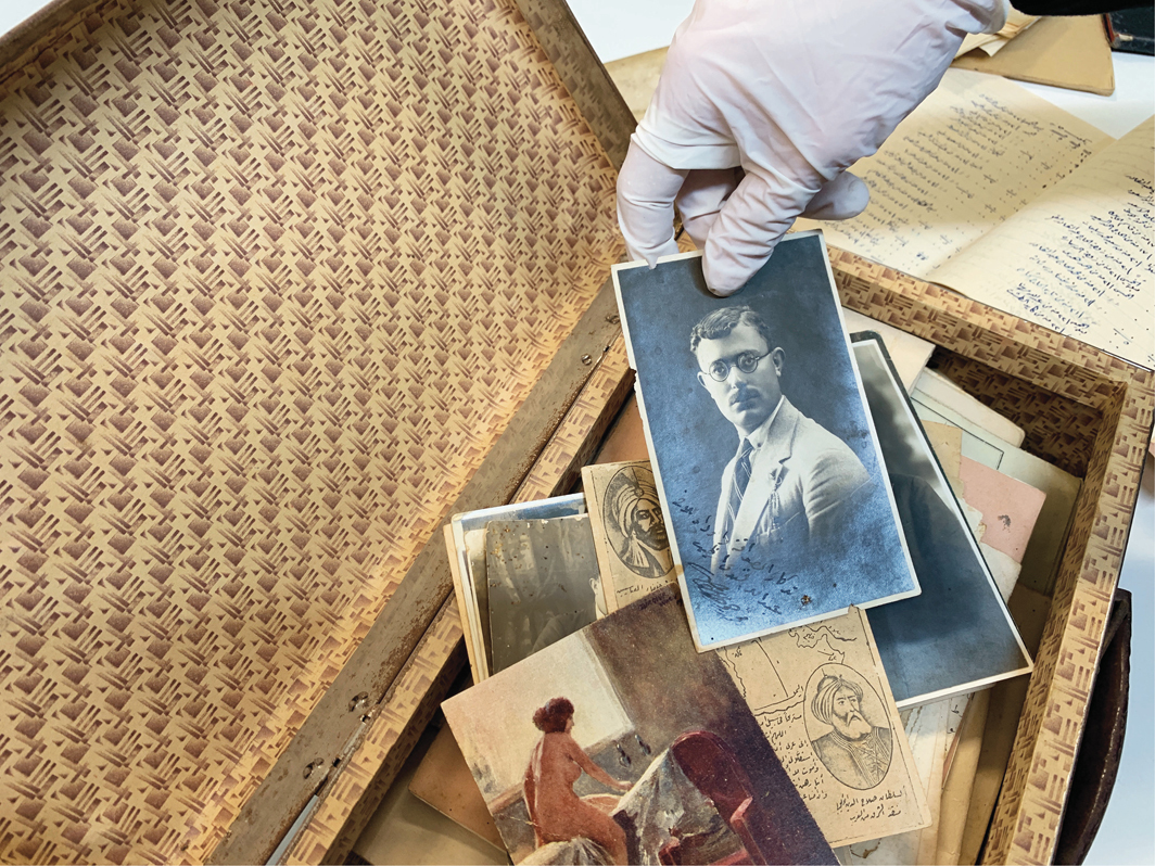 A researcher sorts through the Sakhr al-Khateeb collection of photographs and ephemera that date back to the 1920s, January 2019. From the Palestinian Museum Digital Archive. Photo: Haneed Saleh.
