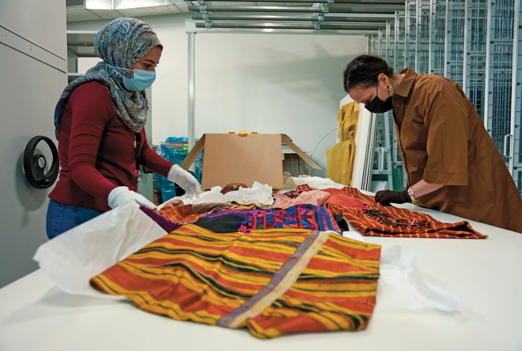 Palestinian Museum conservators examine Palestinian embroidered thobes [traditional men's garments] and accessories from the permanent collection, Palestinian Museum, Birzeit, March 2021. Photo: Hareth Yousef.