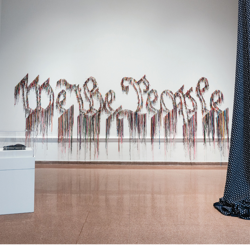 """View of """"Promise, Witness, Remembrance,"""" 2021, Speed Art Museum, Louisville, KY. From left: Bethany Collins, The Star Spangled Banner: A Hymnal, 2020; Nari Ward, We the People, 2011; Hank Willis Thomas, 15,433 (2019), 2021. Photo: Bill Roughen."""