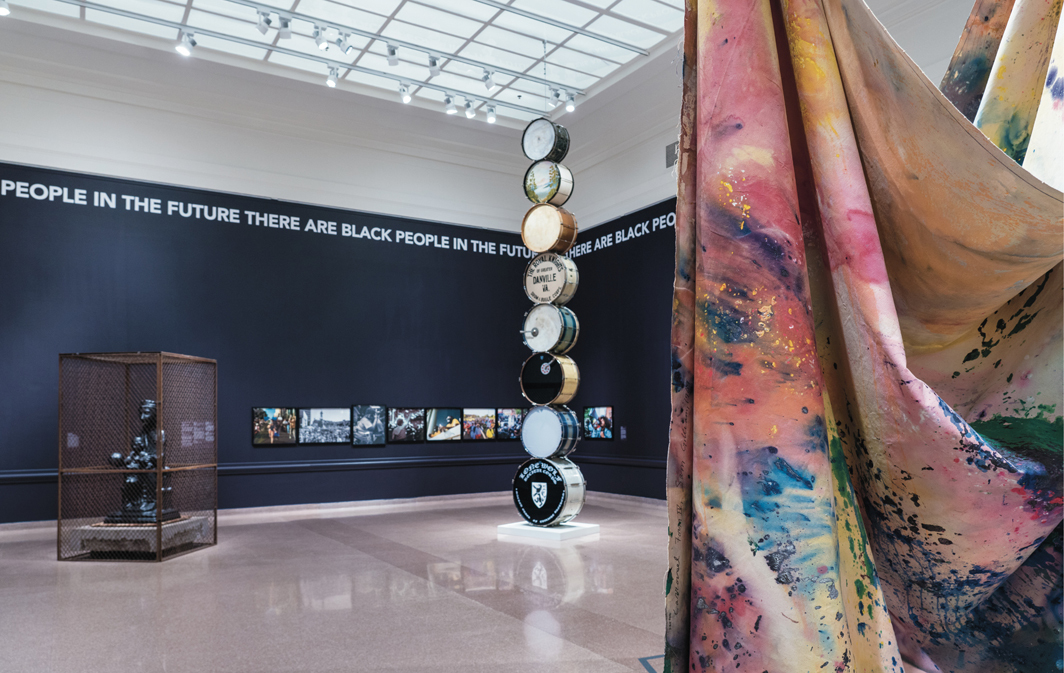 """View of """"Promise, Witness, Remembrance,"""" 2021, Speed Art Museum, Louisville, KY. Foreground, from left: Theaster Gates, Alls my life I has to fight, 2019; Terry Adkins, Muffled Drums (from Darkwater), 2003; Sam Gilliam, Carousel Form II, 1969. Photo: Bill Roughen."""