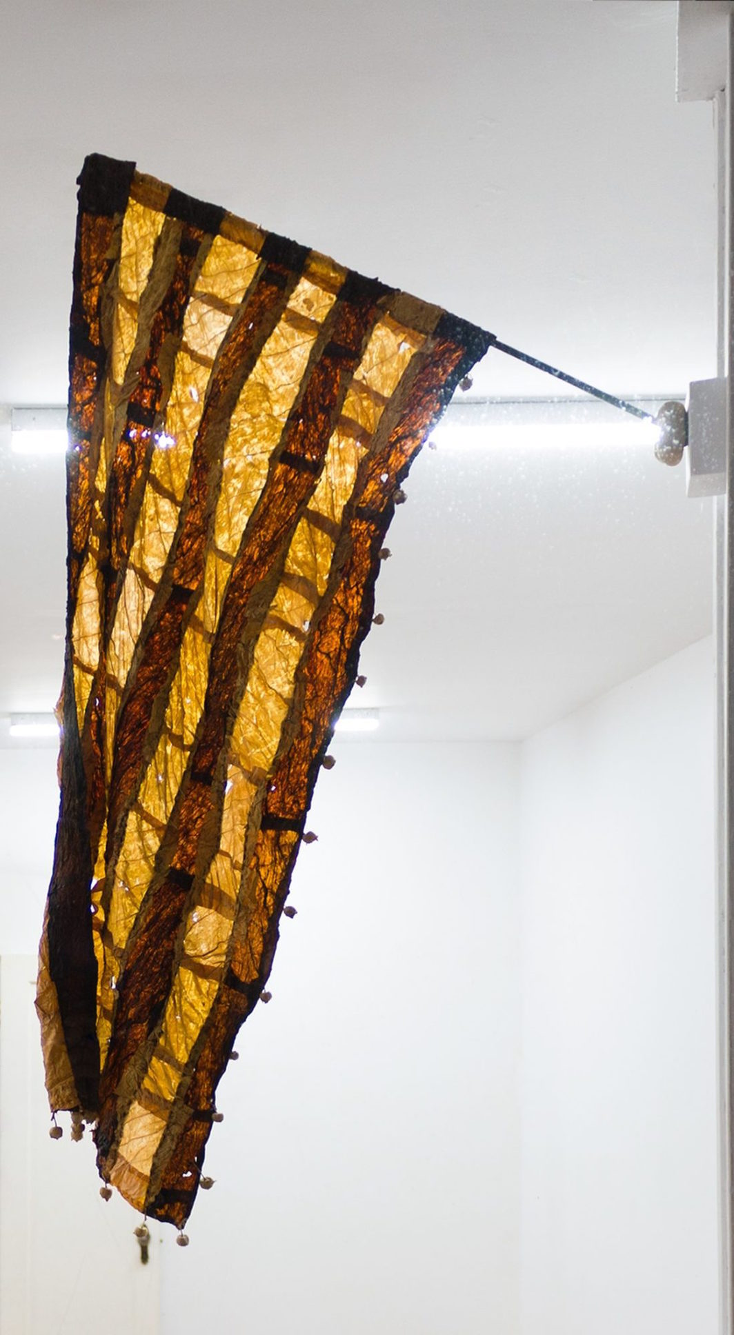 """Gabrielle L'Hirondelle Hill, Dispersal, 2019, Virginia tobacco, Perique tobacco, thread, seed pods, support stocking, and found pole, 43 x 14 5/16""""."""