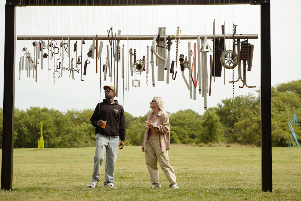 Visitors to the Ranch view a Virginia Overton wind chime, with Aaron Curry sculptures in the background.