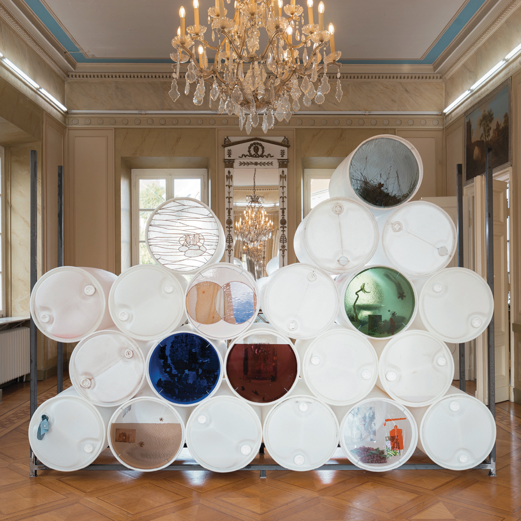 """Nadia Belerique, HOLDINGS (Ongoing), 2020, plastic barrels, metal frame, stained glass, lead, copper tape, fabrics, photographs, rainwater, paint, various objects. Installation view, Kunstverein Braunschweig, Germany, 2020–21. Photo: Stefan Stark. From the 2021 Triennial: """"Soft Water Hard Stone."""""""